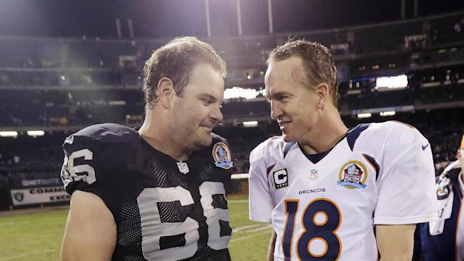 Denver Broncos quarterback Peyton Manning, right, is greeted by Oakland Raiders guard Cooper Carlisle, left, at the end of their NFL football game in Oakland, Thursday, Dec. 6, 2012. Denver won 26-13. (AP Photo/Marcio Jose Sanchez)