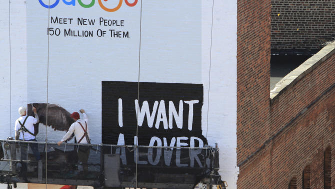 In this April 17, 2012 photo, Art Pastusak, left, and his apprentice Liam McWilliams, paint a billboard on a brick wall in New York. Pastusak, a billboard artist since 1977 has taken McWilliams, 23, a 2010 graduate of Pratt University, as his apprentice in August 2011. Their nostalgic form of advertising is thriving again in New York City. (AP Photo/Bebeto Matthews)