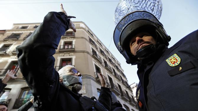 A demonstrator faces of with a policeman during a protest against the Spanish government's new anti-protest law in Madrid