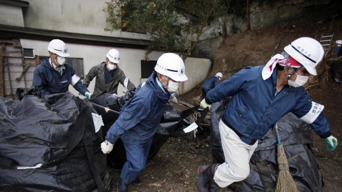 In this Wednesday, March 6, 2013 photo, workers haul a bag of radiation-contaminated leaves during a cleanup operation in the abandoned town of Naraha, just outside the exclusion zone surrounding the Fukushima Dai-ichi nuclear plant in Japan.  Two years after the triple calamities of earthquake, tsunami and nuclear disaster ravaged Japan's northeastern Pacific coast, radioactive and chemical contamination remains a threat. (AP Photo/Greg Baker)