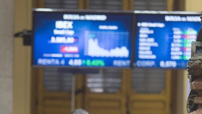 A broker walks around in the stock exchange in Madrid, Spain Tuesday March 26, 2013. Spain's central bank is predicting a continuing recession and mounting unemployment for the rest of 2013 as the country struggles to free itself from a broad European slowdown and repair its finances. The Bank of Spain said Tuesday it expects the country's economy to shrink 1.5 percent this year, compared with 1.4 percent in 2012, and only return to growth in late 2014.(AP Photo/Paul White)