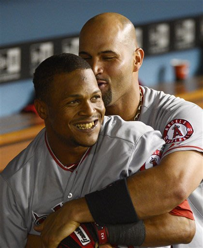 Angels Erick Aybar (in front) and Albert Pujols have a familial bond. (AP)