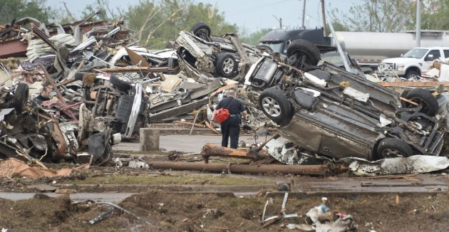 A rescue worker looks for victims in the Moore Hospital parking lot after being hit by a tornado that destroyed buildings and overturned cars in Moore