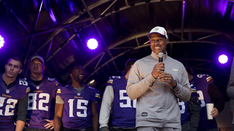 Minnesota Vikings' head coach Leslie Frazier speaks on stage flanked