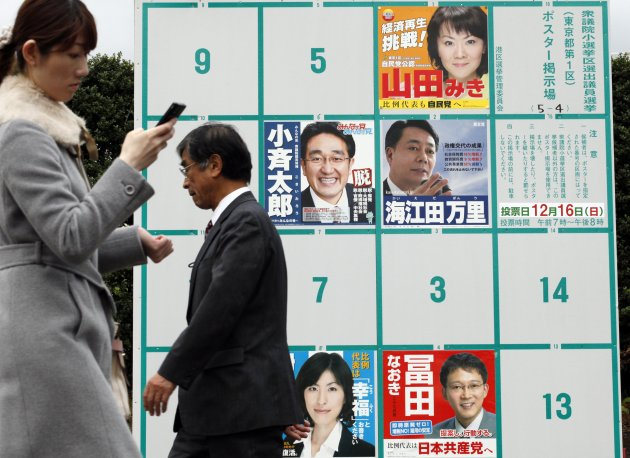 People walk by candidates' poster boards for parliamentary elections in Tokyo Tuesday, Dec. 4, 2012. Leaders for Japan's biggest political parties kicked off Tuesday the campaign for parliamentary elections to be held in less than two weeks with visits to nuclear crisis-hit Fukushima prefecture. (AP Photo/Koji Sasahara)