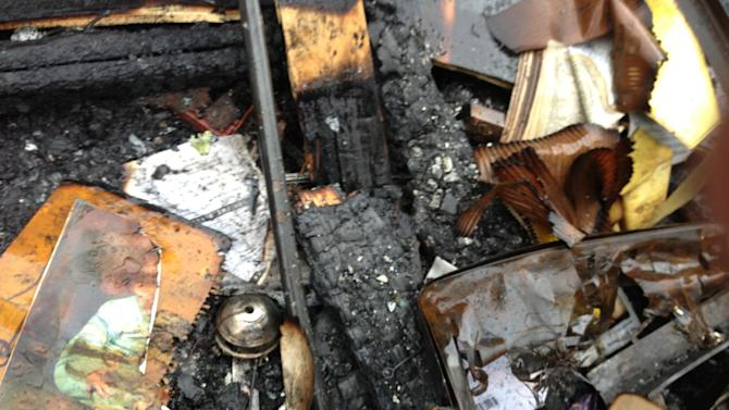 A partially burned child's photo is seen Monday, March 11, 2013, in the debris of a house fire in which seven people were killed Saturday in southeastern Kentucky. Officials say two adults and five children were killed in the fire in Gray, Ky. (AP Photo/Brett Barrouquere)