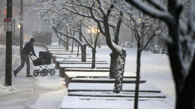 A man wheels a stroller through snow in the Boston Commons early Friday evening, Feb. 8, 2013 in Boston. Snow began falling across the Northeast on Friday, ushering in what was predicted to be a huge, possibly historic blizzard and sending residents scurrying to stock up on food and gas up their cars. The storm could dump 1 to 3 feet of snow from New York City to Boston and beyond.  (AP Photo/Gene J. Puskar)
