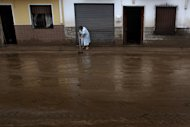A women cleans a muddy street after flash floods in the town of Villanueva del Rosario, Malaga, southern Spain, Friday, Sept. 28, 2012. Homes were destroyed and at least one woman was killed. Rescue workers are searching to determine if there are more victims.(AP Photo/Sergio Torres)