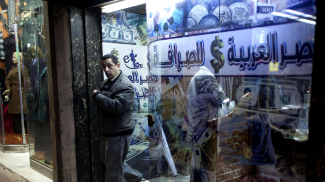 "FILE - In this Sunday, Jan. 6, 2013 file photo, an Egyptian man leaves after changing foreign currency at a currency exchange office, Arabic reads, ""Arabian Egypt for Exchange,"" in Cairo, Egypt. Egypt's foreign currency reserves fell nearly 10 percent in a single month in January, according to figures released by the central bank Tuesday, Feb. 5, 2013, that provided stark new evidence of a dangerous deterioration in the economy amid political turmoil on the streets. (AP Photo/Nasser Nasser, File)"