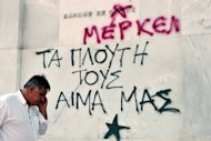 <p>A passerby is seen next to the Bank of Greece sign, where the word 'Greece' has been spray-painted over and the word 'Merkel' written below, in central Athens, on September 27.</p>