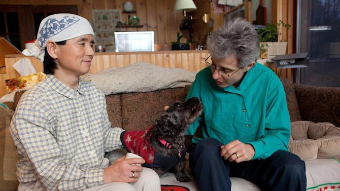 FILE - In this Dec. 21, 2011 file photo, Frances Herbert, right, and her wife, Takako Ueda, of Japan, pose for photos with their dog, Little Bear, at their home in Dummerston, Vt. Latino and gay rights groups that have spent the last several years working to forge a mutually beneficial alliance face a crucial test in the months ahead as immigration reform returns to the top of Washington's agenda. Gay rights advocates are fighting to ensure that the comprehensive immigration legislation high-ranking U.S. senators and President Barack Obama have pledged to pursue includes legal residency options for foreigners in same-sex marriages. (AP Photo/Matthew Cavanaugh)