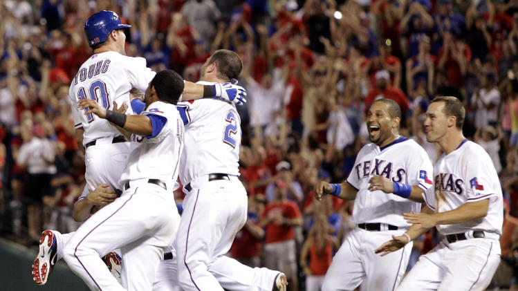 Texas Rangers' Michael Young (10) is carried on the field after hitting a game-winning single that scored Craig Gentry off a pitch from Toronto Blue Jays' Jon Rauch during a baseball game, Saturday, July 23, 2011, in Arlington, Texas. The Rangers won 5-4. (AP Photo/Tony Gutierrez)