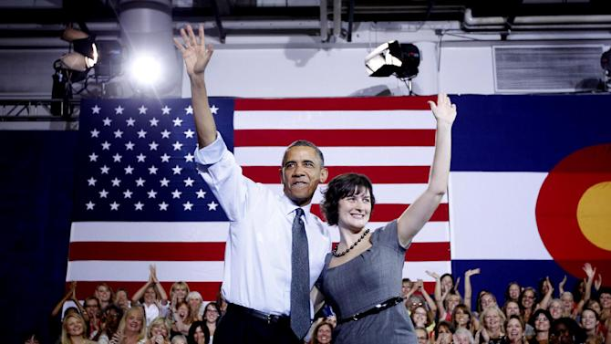 President Barack Obama, accompanied by Sandra Fluke, waves at a campaign in Denver, Wednesday, Aug. 8, 2012. Fluke is a Georgetown law student who inadvertently gained notoriety when talk show host Rush Limbaugh spoke disparagingly of her testimony before Congress on the issue of contraception and insurance coverage. (AP Photo/Pablo Martinez Monsivais)