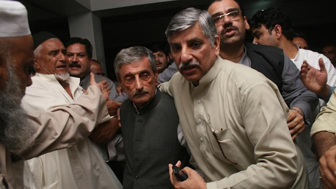 People escort a shocked Pakistani politician, Ghulam Ahmed Bilour, center, who survived a suicide attack, at a local hospital in Peshawar, Pakistan on Tuesday, April 16, 2013. A suicide bomber targeting members of an anti-Taliban political party in northwestern Pakistan killed many people and wounded others, police and hospital officials said. (AP Photo/Mohammad Sajjad)