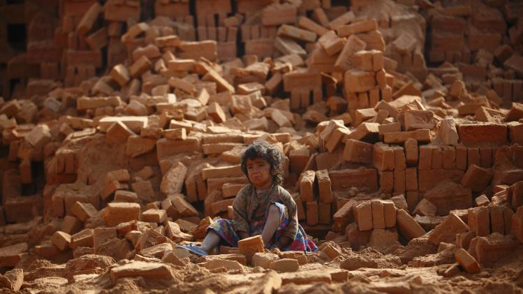A child cries as her mother works to earn money by carrying bricks at a brick factory in Lalitpur
