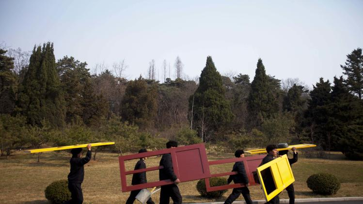 In this April 13, 2011 photo, workers carry painted doors along a road in Mangyongdae, North Korea. (AP Photo/David Guttenfelder)
