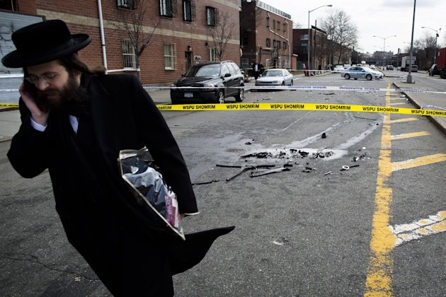 A man walks past debris from a fatal accident that claimed the lives of two expectant parents on their way to the hospital early, Sunday, March 3, 2013, in the Brooklyn borough of New York. A driver s