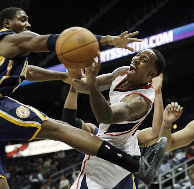 Atlanta Hawks point guard Jeff Teague (0) passes the ball as Indiana Pacers center Ian Mahinmi, left, defends in the second half of a preseason NBA basketball game Tuesday, Oct. 22, 2013, in  Atlanta