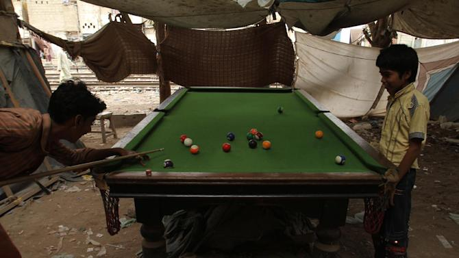 Children play snooker in a poor area of Karachi, Pakistan, Tuesday, July 7, 2015.  Heavy monsoon rains in Pakistan have caused flash floods in some areas, with at least five people reported dead near the capital, Islamabad, according to Waqas Rehman, a spokesman at the government-run emergency service, Tuesday. (AP Photo/Fareed Khan)