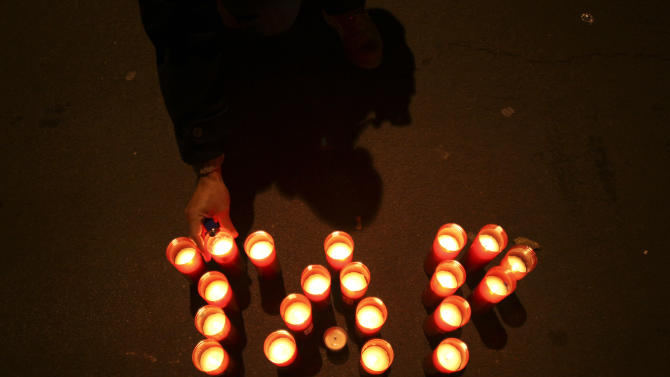 A Portuguese state airline TAP Air Portugal's worker places candles that form the word TAP during a vigil outside the Portuguese cabinet meeting building against the privatization of the company, Wednesday, Dec. 19, 2012. The Portuguese government plans to sell the company as part of an economic recovery program linked to a euro 78 billion ($102 billion) bailout needed last year. (AP Photo/Francisco Seco)