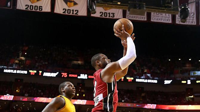 Dwyane Wade (R) of the Miami Heat shoots over Dion Waiters of the Cleveland Cavaliers during their NBA game at the American Airlines Arena in Miami, Florida, on December 25, 2014