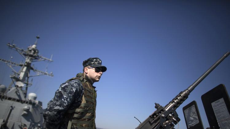 A U.S. Navy personnel stands guard near a machine gun on board the USS Truxtun at the Black Sea port of Varna