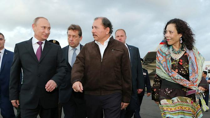 FILE - In this July 11, 2014 handout file photo, Nicaragua's President Daniel Ortega, center, and first lady Rosario Murillo walk with Russia's President Vladimir Putin, left, upon his arrival at the international airport, in Managua, Nicaragua. Her husband is Nicaragua's head of state, but as Chief of Communications, Murillo is the voice and the other face of the Ortega government. (AP Photo/Nicaragua Presidential Press Office, Cesar Perez, File)
