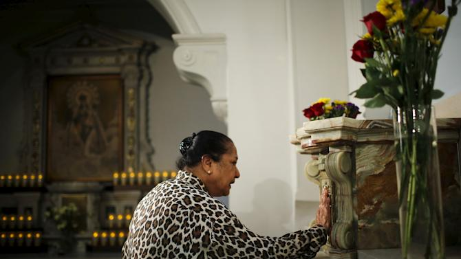 A woman prays while people attend the last mass at Church of Our Lady of Peace in New York