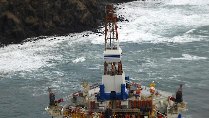 In this image provided by the U.S. Coast Guard the conical drilling unit Kulluk sits grounded 40 miles southwest of Kodiak City, Thursday, Jan. 3, 2012. The Kulluk grounded after many efforts by tug vessel crews and Coast Guard crews to move the vessel to safe harbor during a winter storm.Calls for federal scrutiny of Royal Dutch Shell PLC drilling operations in Arctic waters swelled Thursday with a request for a formal investigation by members of Congress. (AP Photo/U.S. Coast Guard, Petty Officer 2nd Class Zachary Painter)