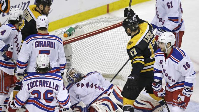 Boston Bruins left wing Milan Lucic (17) raises his stick to celebrate a goal by teammate Zdeno Chara (not shown) as New York Rangers goalie Henrik Lundqvist, center, falls onto his back during the second period in Game 1 of an NHL hockey playoffs Eastern Conference semifinal game in Boston, Thursday, May 16, 2013. (AP Photo/Charles Krupa)