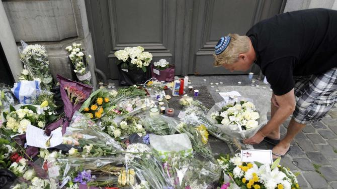 A passer-by puts down flowers at the entrance of the Jewish Museum, site of a shooting in central Brussels