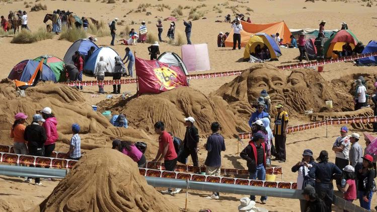 Artists work on sand sculptures depicting scenes from Biblical stories during Holy Week celebrations in Cochiraya