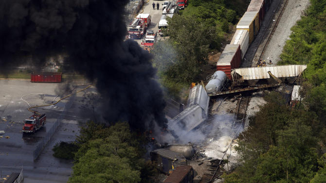FILE- In this Tuesday, May 28, 2013, file photo, a fire burns at the site of a CSX freight train derailment, in Rosedale, Md., where fire officials say the train crashed into a trash truck, causing an explosion that rattled homes at least a half-mile away and collapsed nearby buildings, setting them on fire. The nation's railroads are safer than ever, despite recent high-profile accidents like this week's fiery derailment in Maryland. Derailments and crossing accidents have steadily declined nationwide even as businesses have come to increasingly rely on trains to move their raw materials and products. (AP Photo/Patrick Semansky)