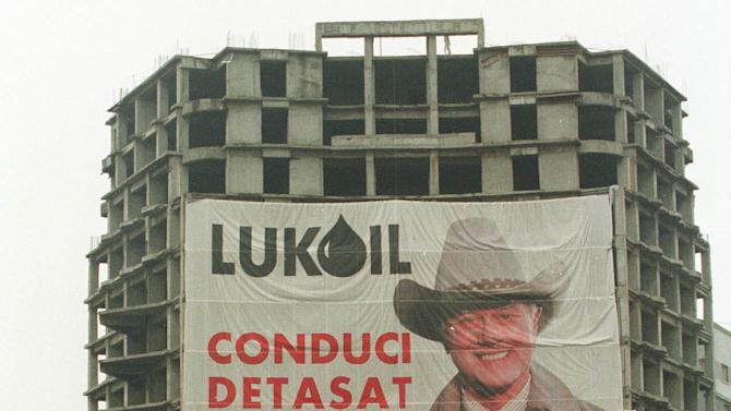 """FILE - In this Thursday Nov. 18, 1999 file photo, people cross the street in downtown Bucharest, Romania near an unfinished apartment building draped with a poster of U.S. actor Larry Hagman as J.R. Ewing from the television show """"Dallas."""" The poster is part of a high-profile advertising campaign for the Russian oil giant Lukoil. """"Dallas"""" was one of the few American TV series the late communist dictator Nicolae Ceausescu allowed to be shown on Romanian television.  Actor Larry Hagman, who for more than a decade played villainous patriarch JR Ewing in the TV soap Dallas, has died at the age of 81, his family said Saturday Nov. 24, 2012.  (AP Photo/Vadim Ghirda)"""