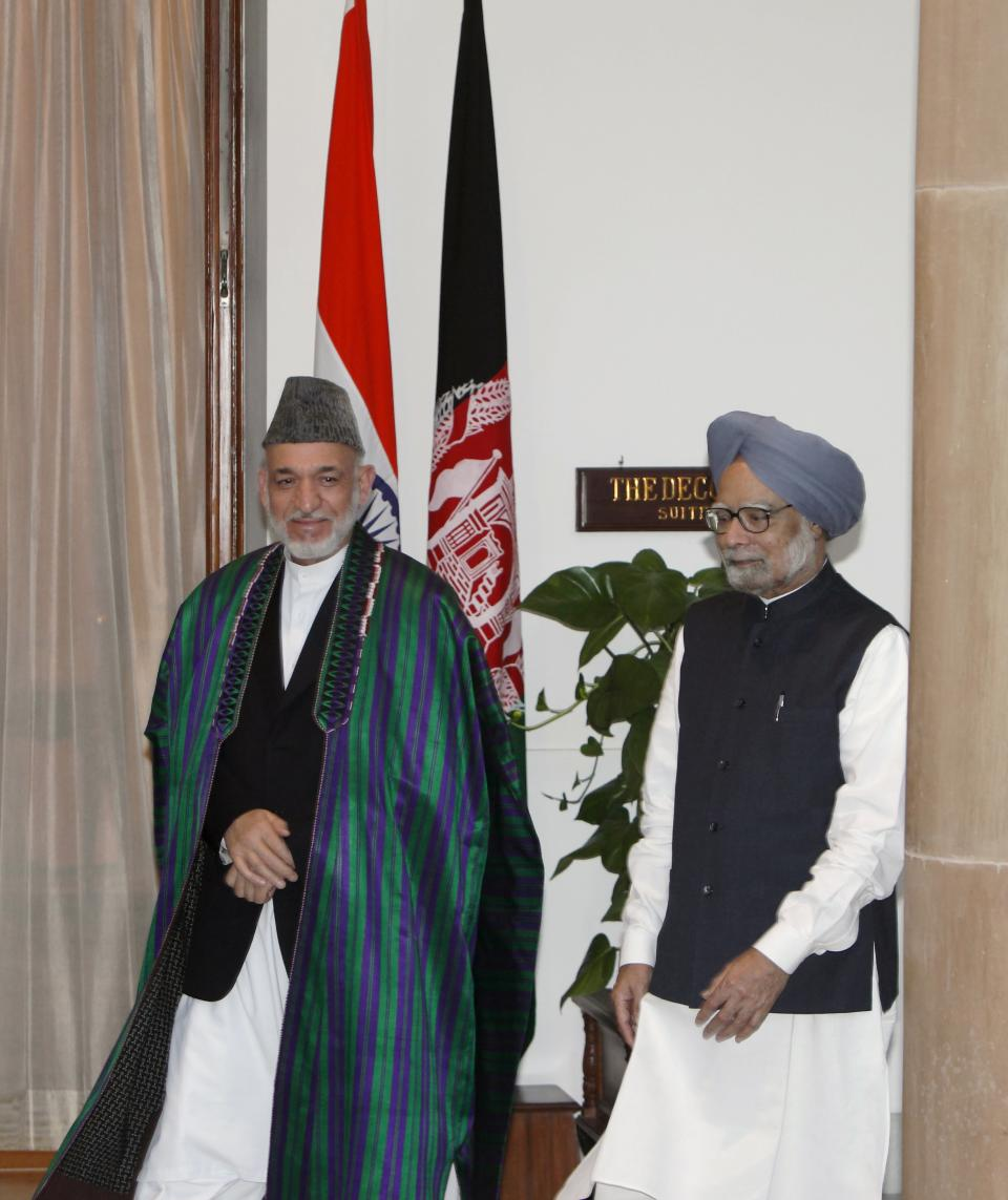 Indian Prime Minister Manmohan Singh, right, and Afghanistan President Hamid Karzai arrive for a meeting in New Delhi, India, Tuesday, Oct. 4, 2011.  Karzai is on a two-day official visit to India.(AP Photo/Gurinder Osan)