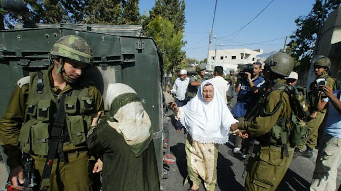 """This undated publicity photo released by Kino Lorber, Inc. shows co-director Emad Burnat's mother, pleading with an Israeli soldier to release her son Khaled after he was arrested, in a scene from the documentary film, """"5 Broken Cameras,"""" by Burnat and co-director, Guy Davidi. (AP Photo/Kino Lorber, Inc.)"""