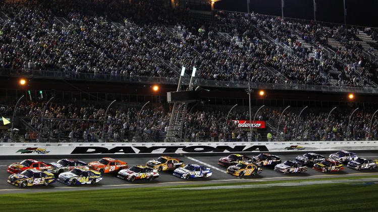 Martin Truex Jr. (56) leads the field to start the NASCAR Budweiser Shootout auto race at Daytona International Speedway, Saturday, Feb. 18, 2012, in Daytona Beach, Fla. (AP Photo/Terry Renna)