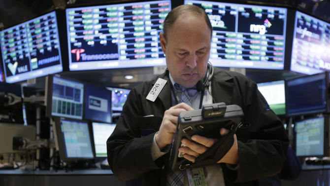 "A trader works on the floor at the New York Stock Exchange in New York, Wednesday, Jan. 2, 2013.   The ""fiscal cliff"" compromise, for all its chaos and controversy, was enough to send the stock market shooting higher Wednesday, the first trading day of the new year. (AP Photo/Seth Wenig)"