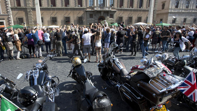 Harley Davidson motorcycles are parked as Pope Francis, top, arrives to celebrate mass in St. Peter's Square, at the Vatican, Sunday, June 16, 2013. Thousands of Harley-Davidson lovers have met in Rome to celebrate the motorcycle company's 110th anniversary. The four-day event includes a major parade through the heart of the city and a blessing by Pope Francis during his Angelus noon prayer at the Vatican on Sunday.  (AP Photo/Andrew Medichini)