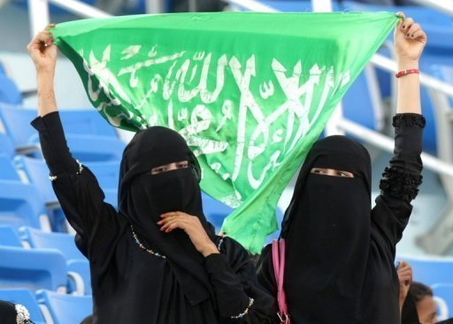Saudi women hold up their national flag as they watch a sports event in the southern Yemeni city of Aden. Two female athletes from Saudi Arabia will compete at the London Games this summer in a historic first for the country, the International Olympic Committee said