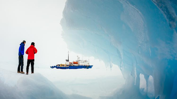 In this Tuesday, Dec. 31, 2013 image provided by Australasian Antarctic Expedition/Footloose Fotography, passengers from the Russian ship MV Akademik Shokalskiy trapped in the ice 1,500 nautical miles south of Hobart, Australia, walk around the ice. Passengers on board a research ship that has been trapped in Antarctic ice for a week are expected to be rescued by helicopter, after three icebreakers failed to reach the paralyzed vessel, officials said Tuesday. (AP Photo/Australasian Antarctic Expedition/Footloose Fotography, Andrew Peacock) EDITORIAL USE ONLY