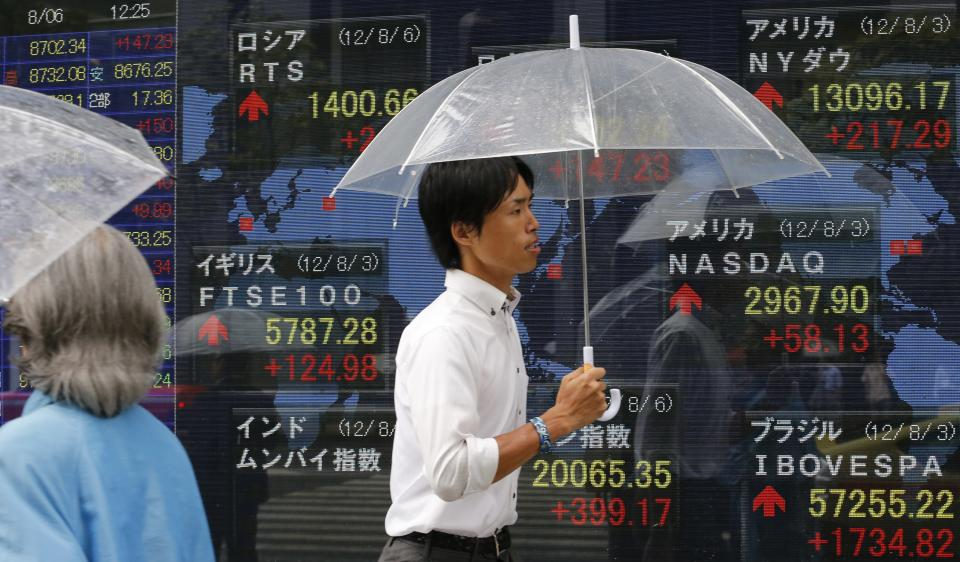 A man walks by an electronic stock indicator in Tokyo Monday, Aug. 6, 2012. Asian stock markets rose sharply in early trading Monday, boosted by stronger-than-expected U.S. hiring figures for July following three months of weak job gains. (AP Photo/Shizuo Kambayashi)