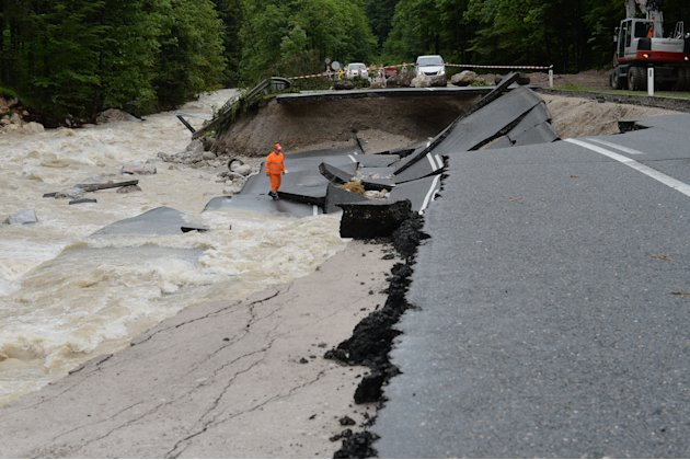 A person looks at the  heavily damaged  road  between Lofer and Waidring in the Austrian province of Tyrol,  Monday, June. 3, 2013. Heavy rainfalls caused floods along rivers and lakes in Germany, Aus