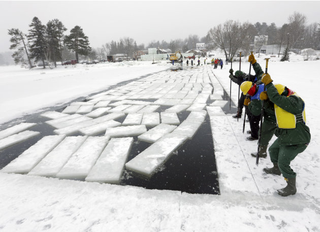 Inmates from the Moriah Shock Incarceration Correctional Facility, wearing green, work with volunteers breaking off ice blocks from Lake Flower that will be used to construct the Saranac Lake Winter C