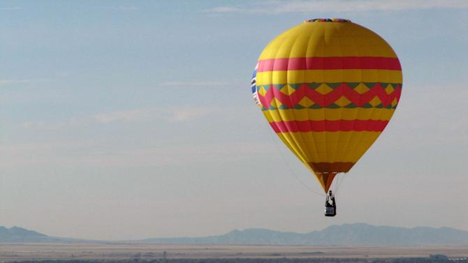 A hot air balloon floats over Albuquerque, N.M., on Tuesday, Oct. 5, 2010. The annual Albuquerque International Balloon Fiesta has attracted about 500 balloons and thousands of spectators. (AP Photo/Susan Montoya Bryan)