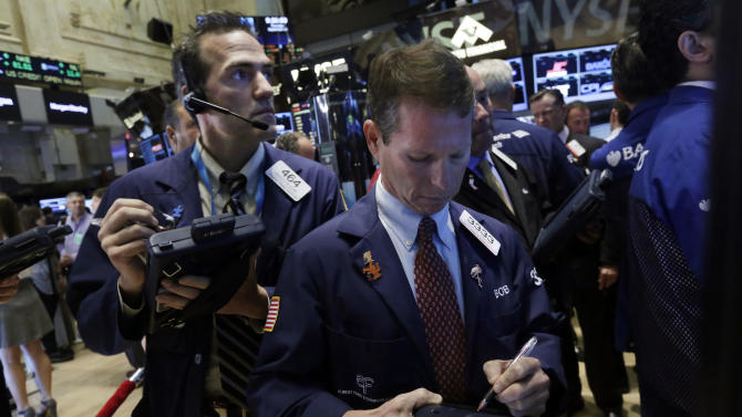 Traders Gregory Rowe, left, and Robert Charmack work on the floor of the New York Stock Exchange Thursday, Sept. 18, 2014. U.S. stocks are opening higher a day after the Federal Reserve made clear it would keep interest rates at record lows for a while. (AP Photo/Richard Drew)