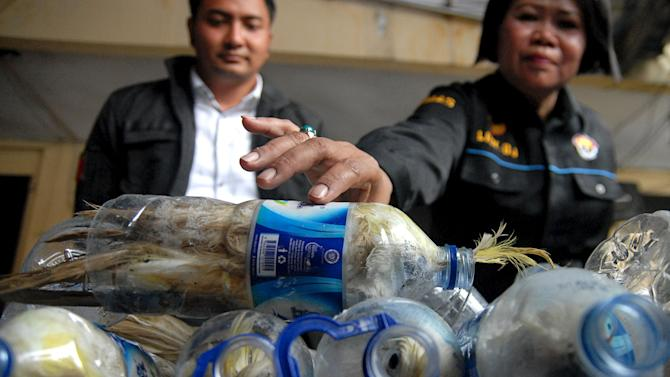 A police officer holds a water bottle which with a yellow-crested cockatoo put inside for illegal trade at the customs office of Tanjung Perak port in Surabaya