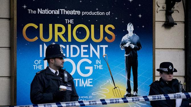 """Police stand outside The Apollo Theatre in London, Friday, Dec. 20, 2013, Authorities are carrying out a structural assessment at the Apollo Theatre after the partial collapse of its ceiling injured more than 75 people in the packed auditorium. An initial report is expected Friday after an overnight survey. The building remains cordoned off after the incident happened during the evening performance of """"The Curious Incident Of The Dog In The Nighttime."""" (AP Photo/Alastair Grant)"""
