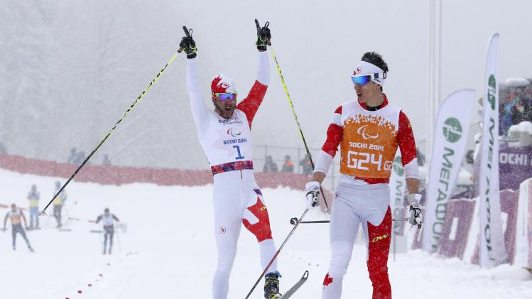 Canada's Mckeever and guide Nishikawa celebrate gold medal during men's 1 km cross-country for visually impaired at 2014 Sochi Paralympic Winter Games in Rosa Khutor