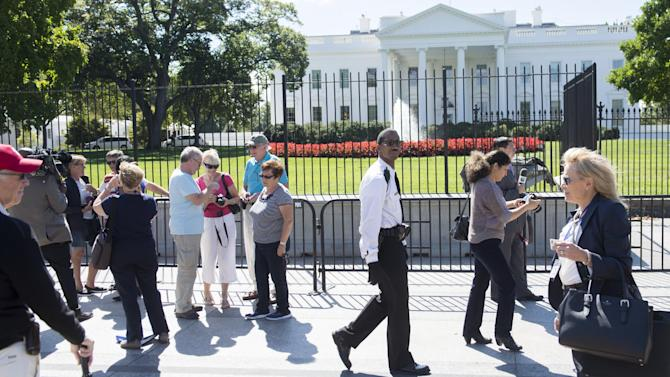 A member of the US Secret Service Uniformed Division patrols alongside tourists outside a temporary fence installed at the White House in Washington on September 22, 2014
